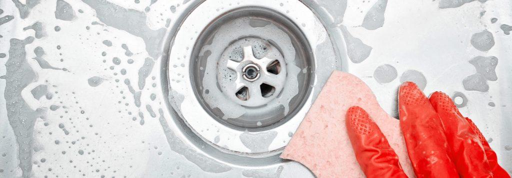 Schwamm reinigt Abfluss einer Spüle