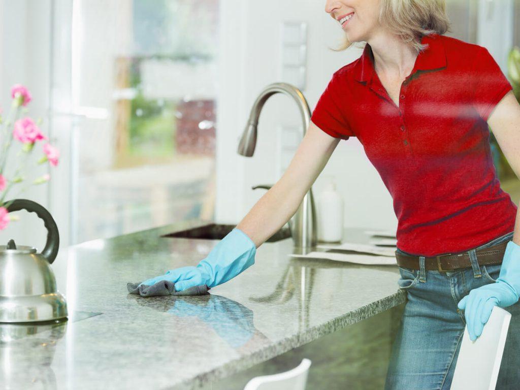 Frau reinigt Küchenarbeitsplatte mit einem Lappen