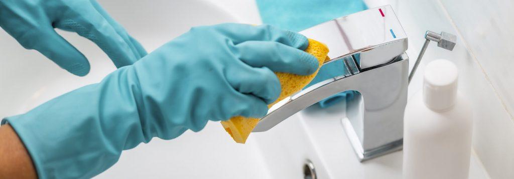 Hände in Handschuhen reinigen Badarmaturen mit einem Schwamm