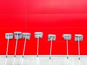 Mehrere Wischmopps stehen aufrecht vor einer roten Wand